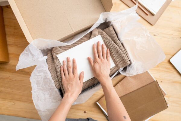 Hands of young manager of online shop putting paper on top of folded sweater